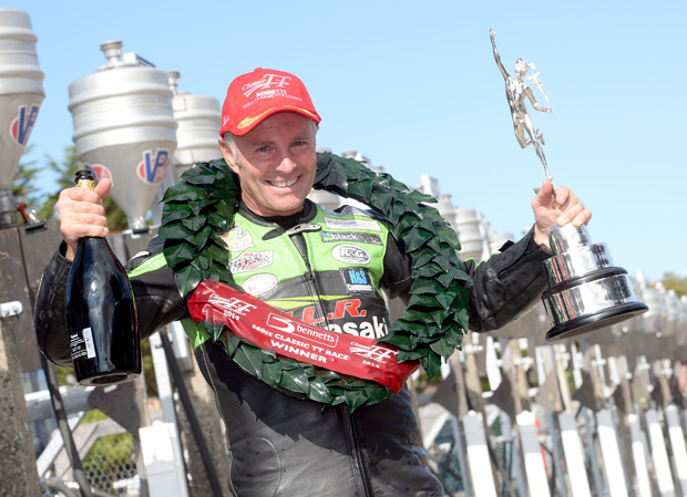 Ian Lougher holding the winner's trophy after winning the 2014 500cc Classic TT
