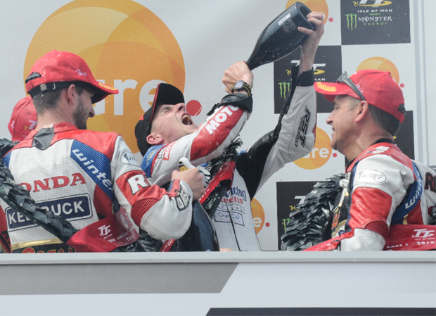 Tom Birchall drinks the winners' champagne on the podium