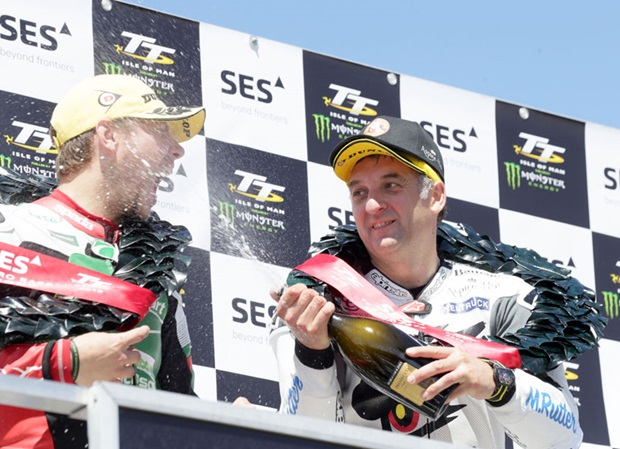Michael Rutter sprays champagne into second placed Daley Mathison's mouth on the SES TT Zero Race podium. Photo Stephen Davison / Pacemaker Press Intl